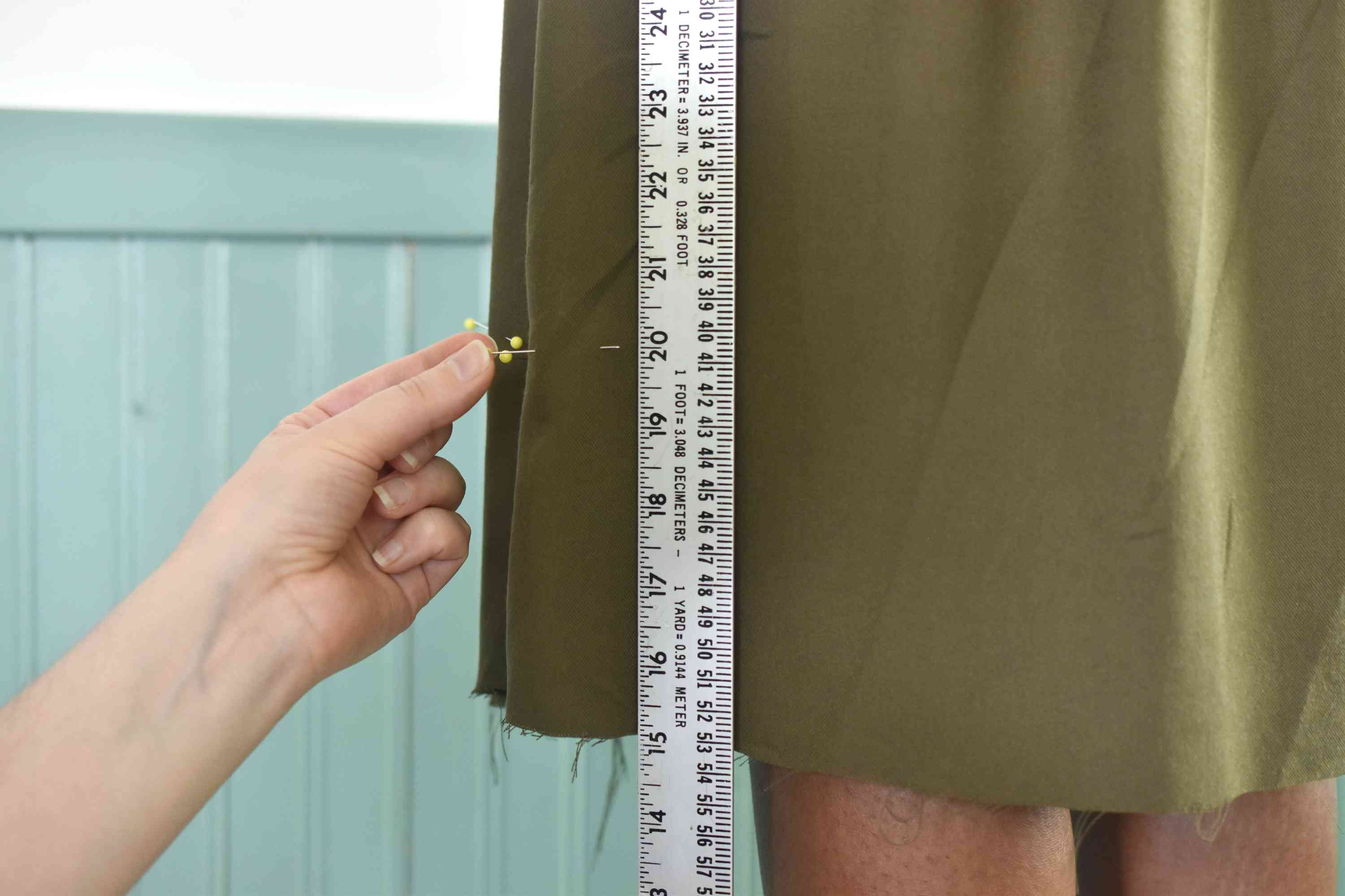 Measuring the hem of a skirt with a yardstick and pins