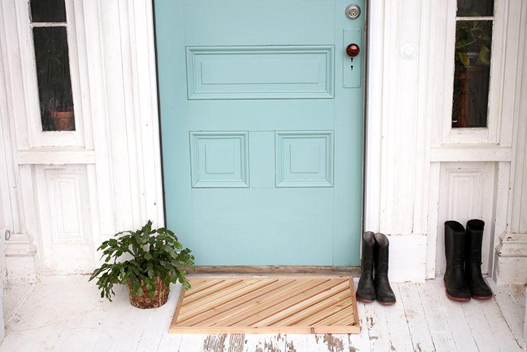A wood door mat in front of a light blue door.