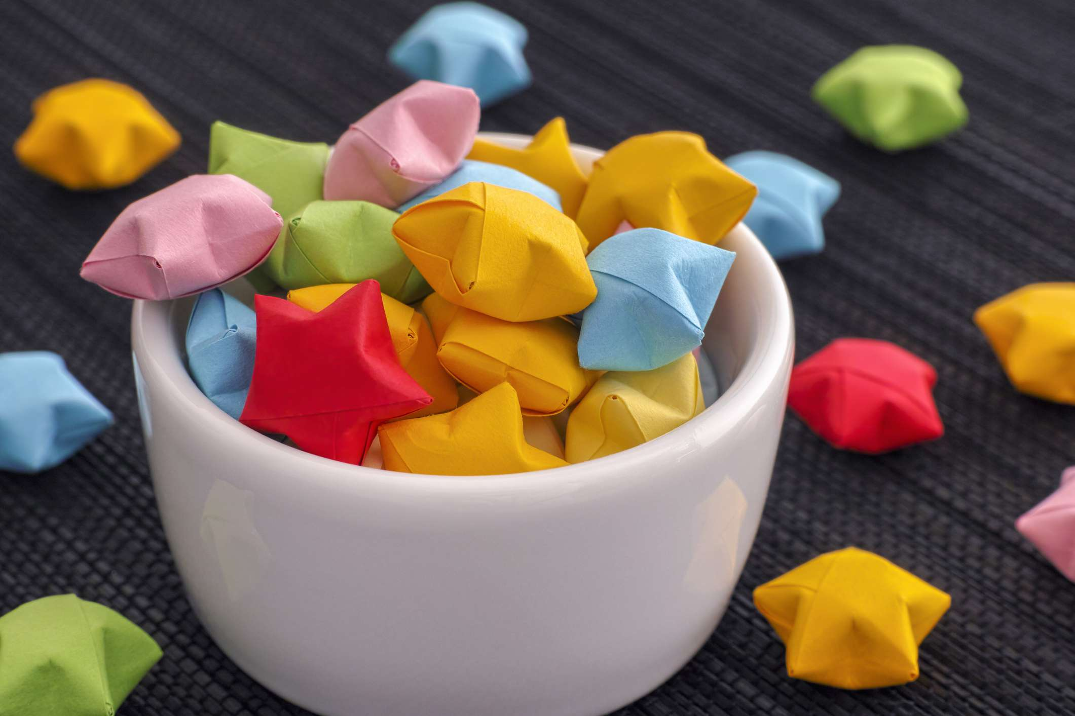 Origami lucky stars spilling out of glass bowl