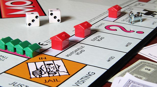 Monopoly board with houses, hotels, pair of dice, and dog token.