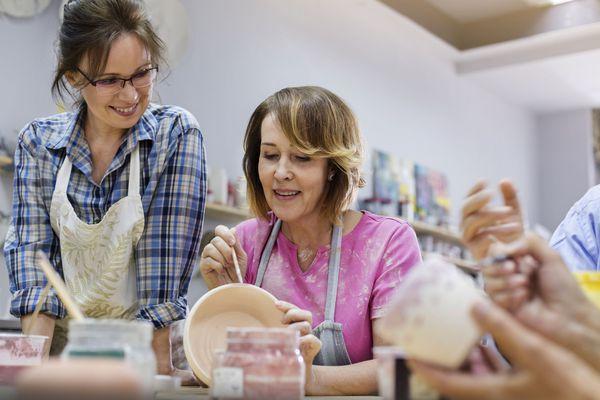 women glazing pottery in studio