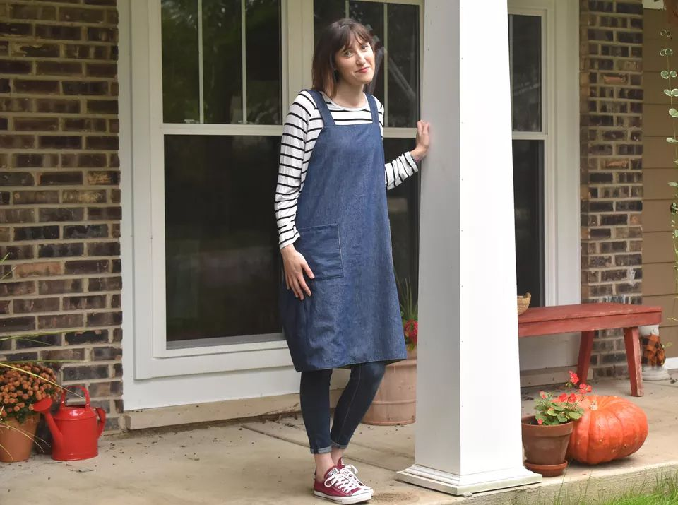 A woman standing on a porch wearing an apron