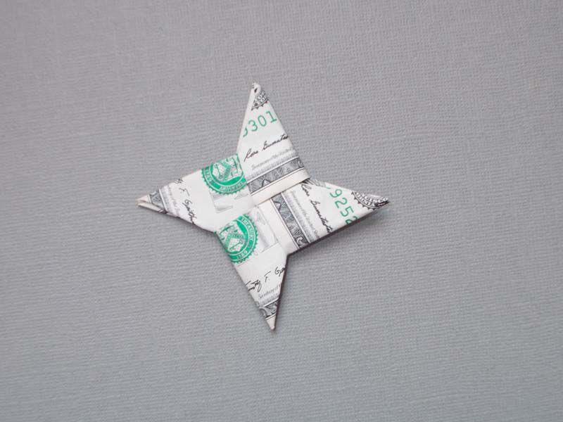 A dollar bill in stage six of an origami star