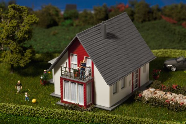A diorama of a family of miniature figurines and their dollhouse