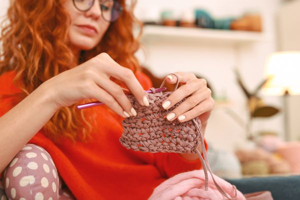 Woman knitting with brown yarn.