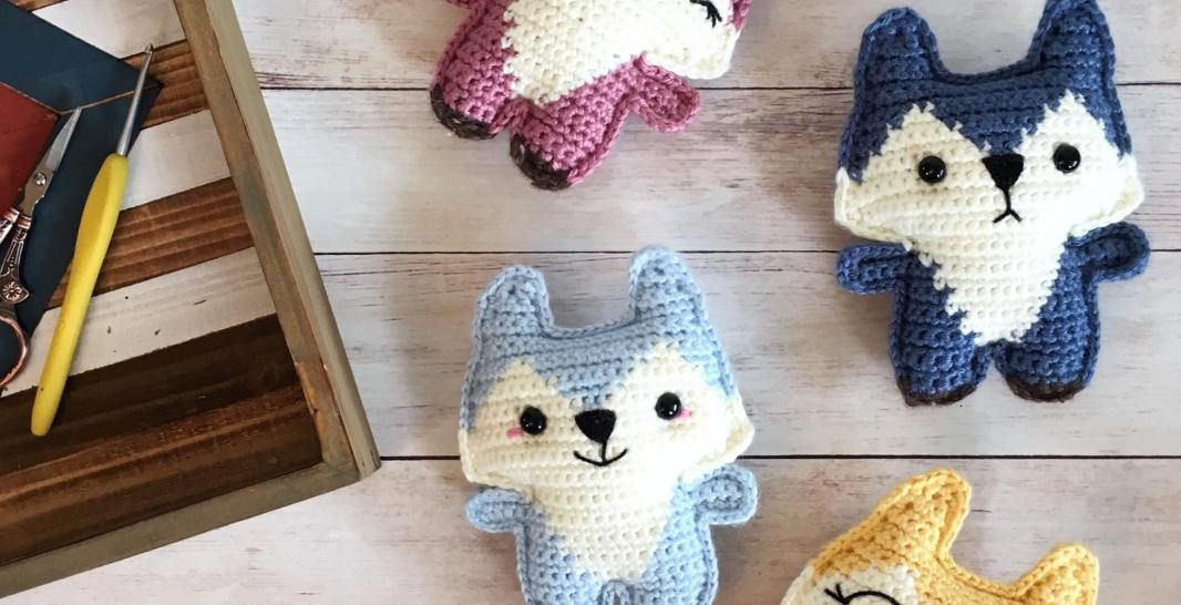 Small crochet foxes of different colors lying on wood floor.