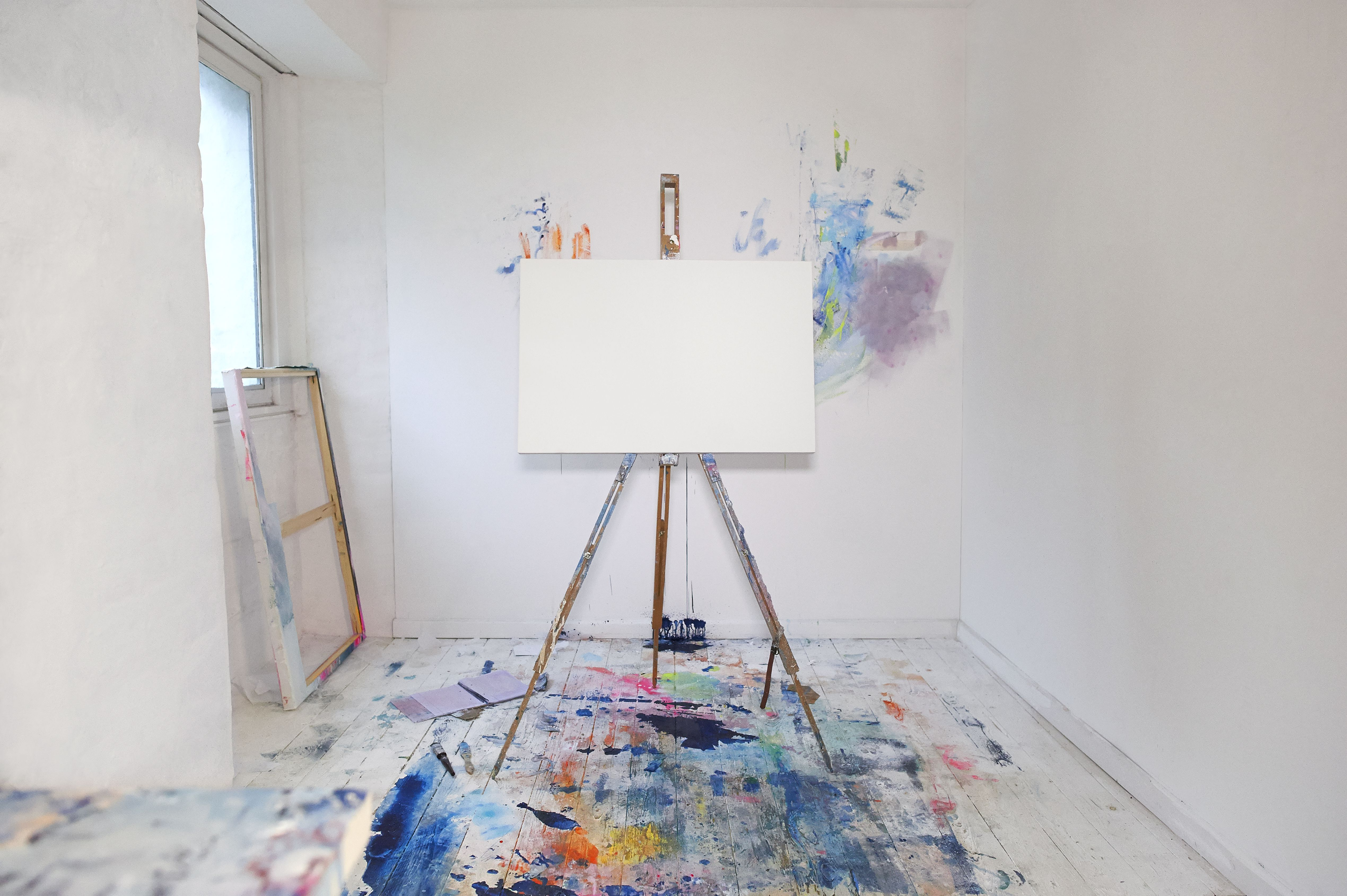 Blank canvas on easel and paint in artist studio.