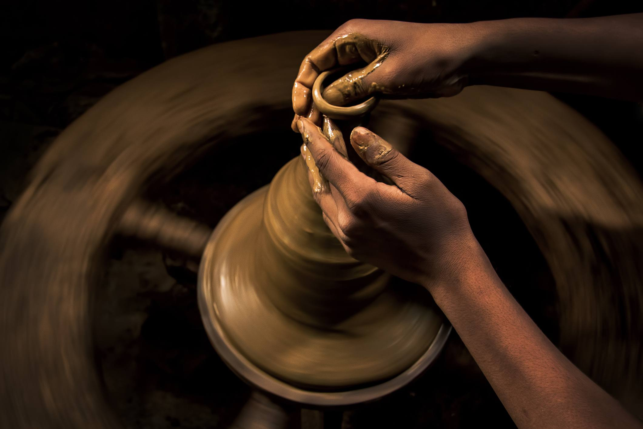 A potter puts the finishing touches on a clay lamp