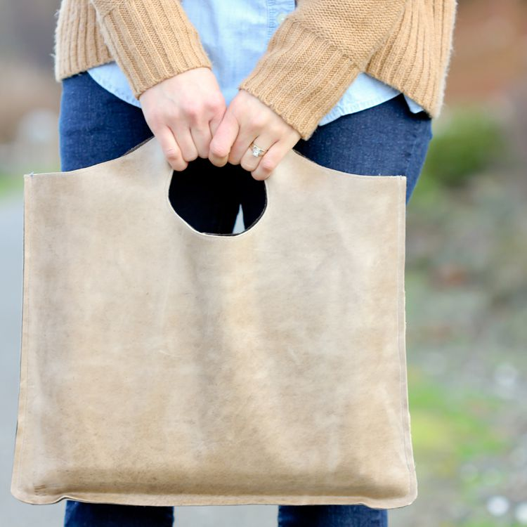 A woman holding a brown leather tote
