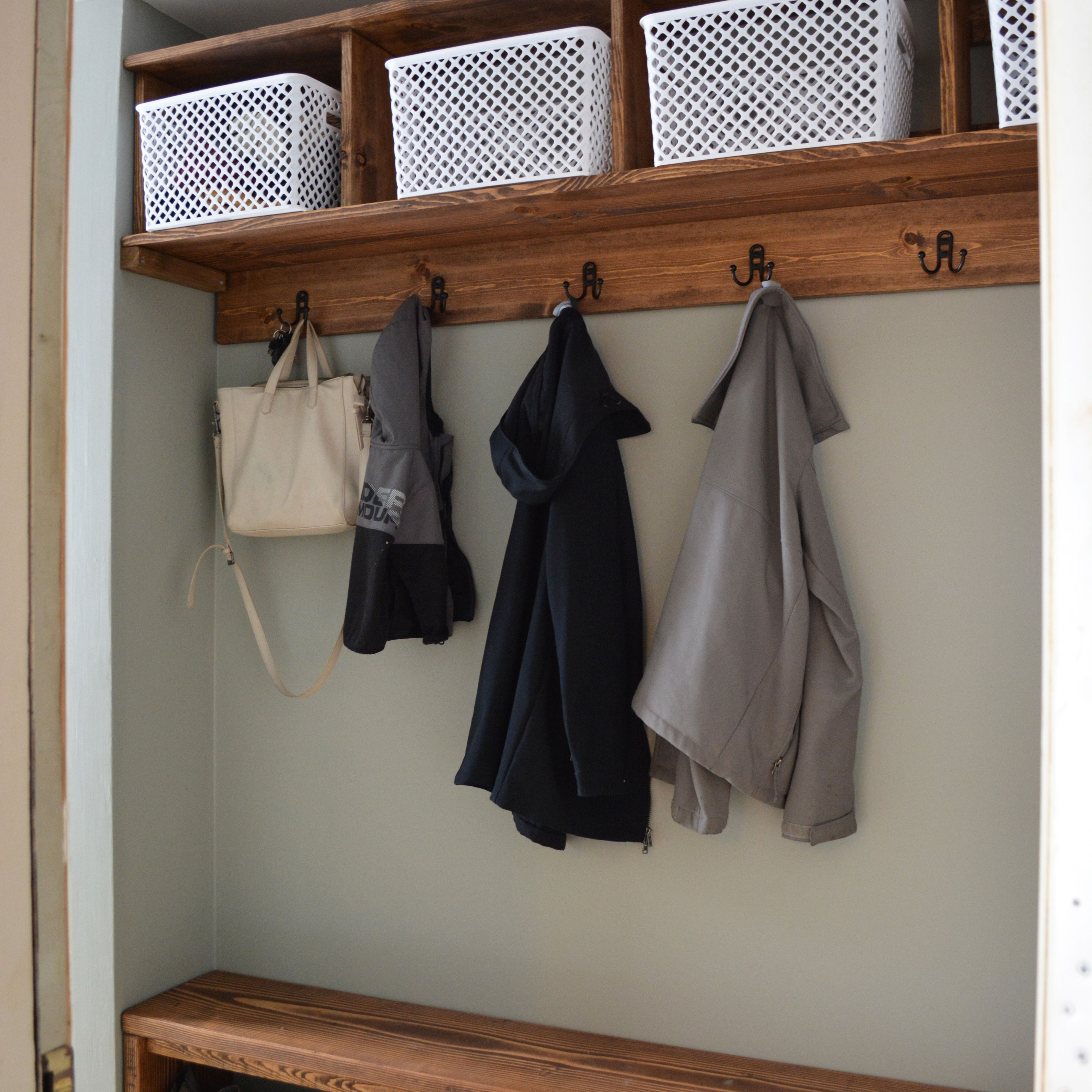 A mudroom with shoe storage on the floor