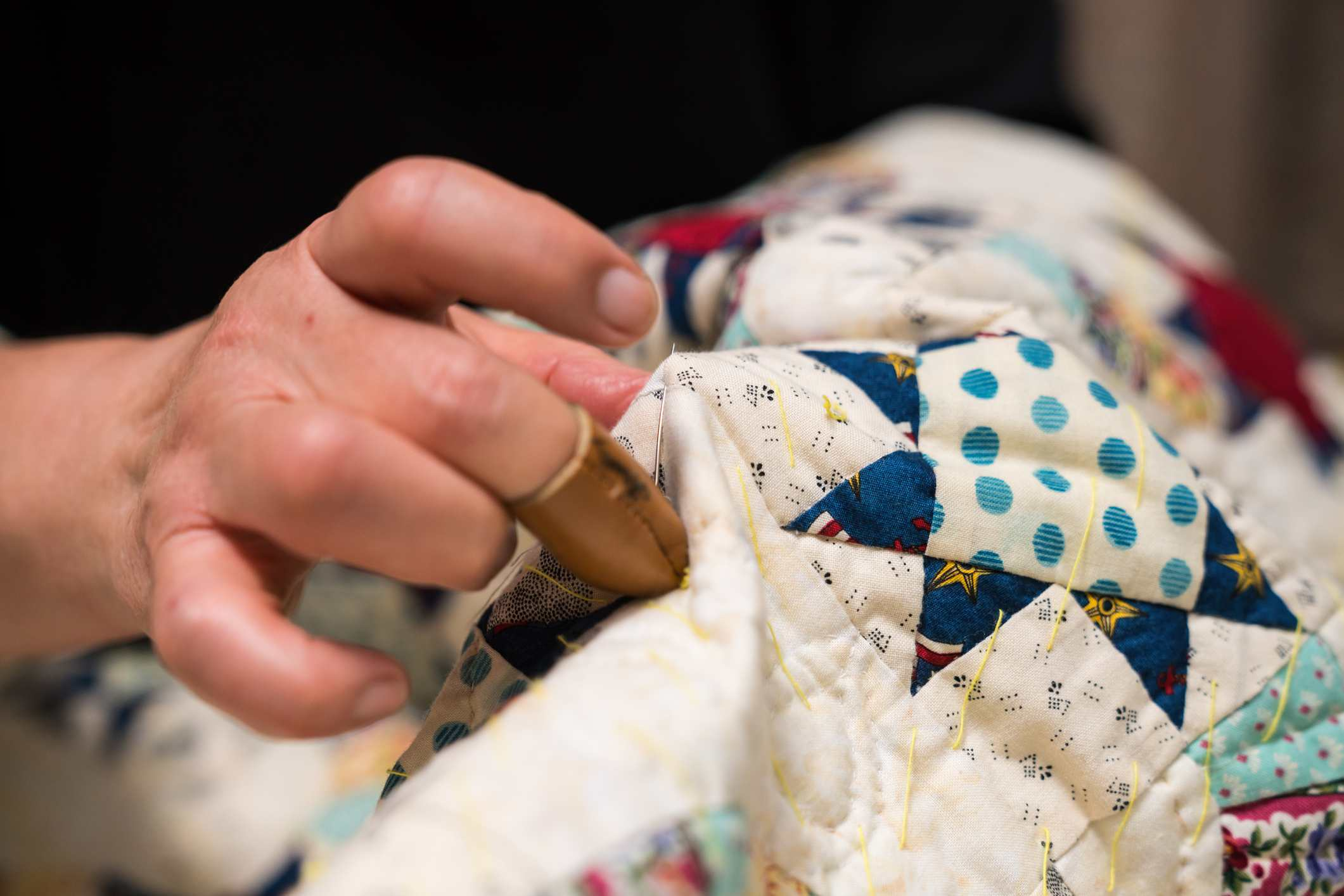 woman sewing sandwich quilt with needle