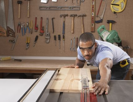 Carpenter cutting wooden plank in a workshop