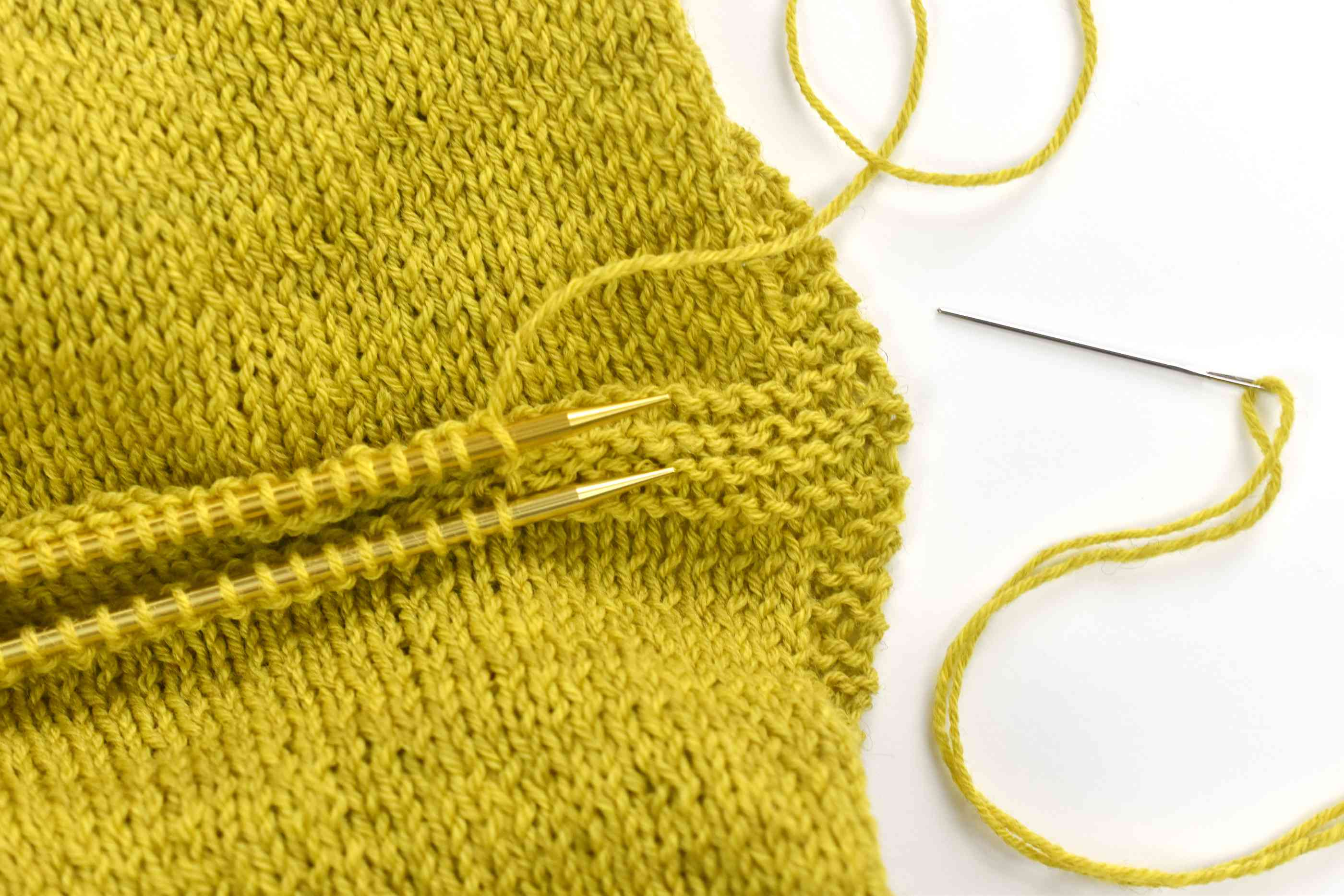 Grafting the shoulders of a tunic together with three needles