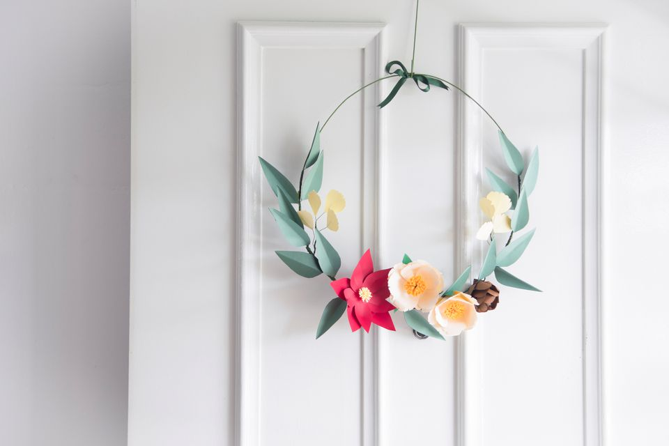 a paper flower wreath hanging from a door