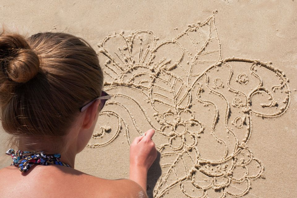 Young girl draws on the sand on the beach a doodle.
