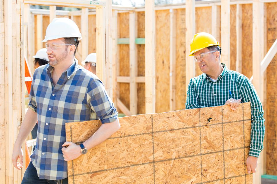 Men carrying plywood on construction site
