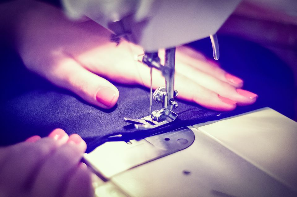 A woman's hands stitching fabric on a sewing machine