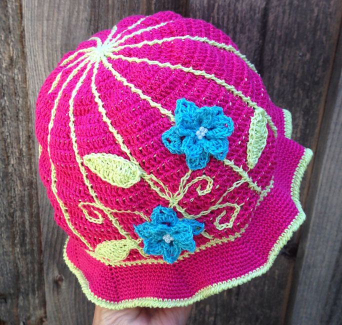 Bright pink floral crochet sunhat with blue flowers and leaves.