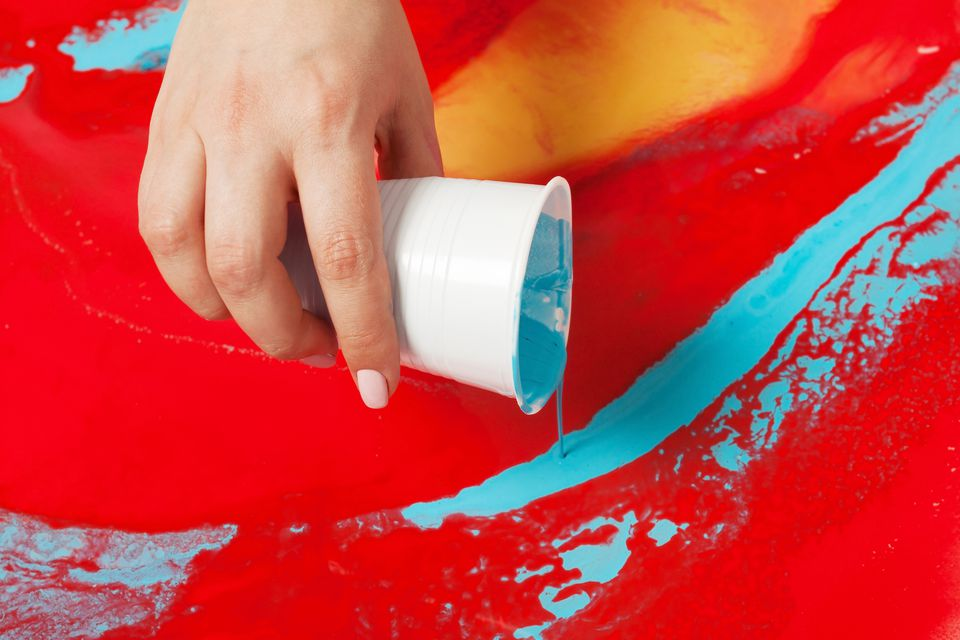 How to make acrylic painting. Work in progress. Female hand holding a plastic cup with blue paint.