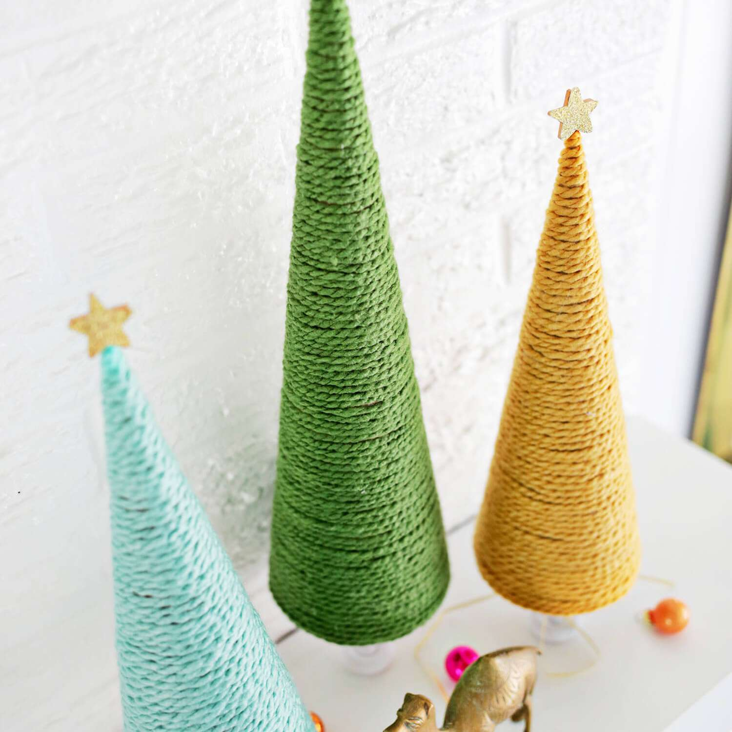 Blue, green and yellow trees made from yarn wrapped around a cone form.