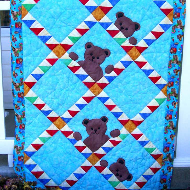 Blue quilt with purple peekaboo bears hanging from clothespins.