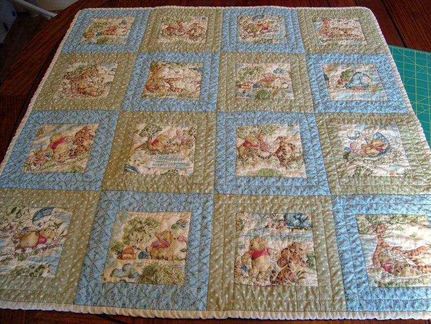 Winnie-the-Pooh baby quilt lying on a table.