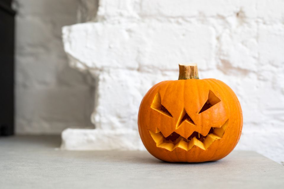 Halloween Pumpkin Lantern in front of a white brick wall