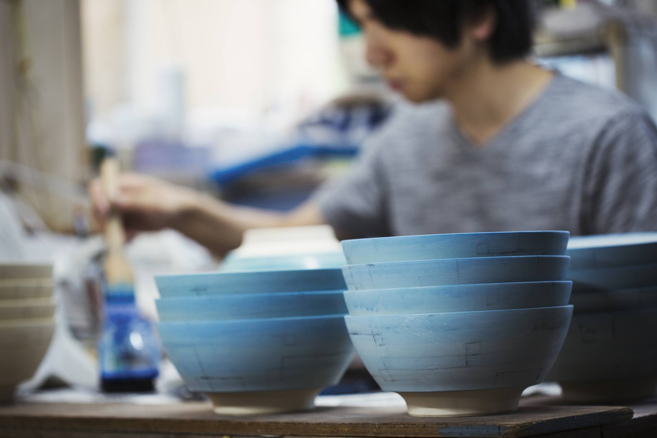 White bowls with a blue glaze in a Japanese porcelain workshop.