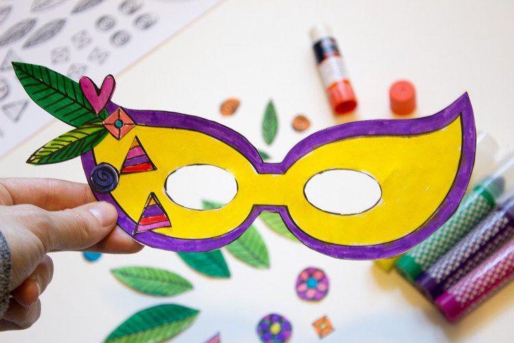 A yellow and purple paper Mardi Gras mask