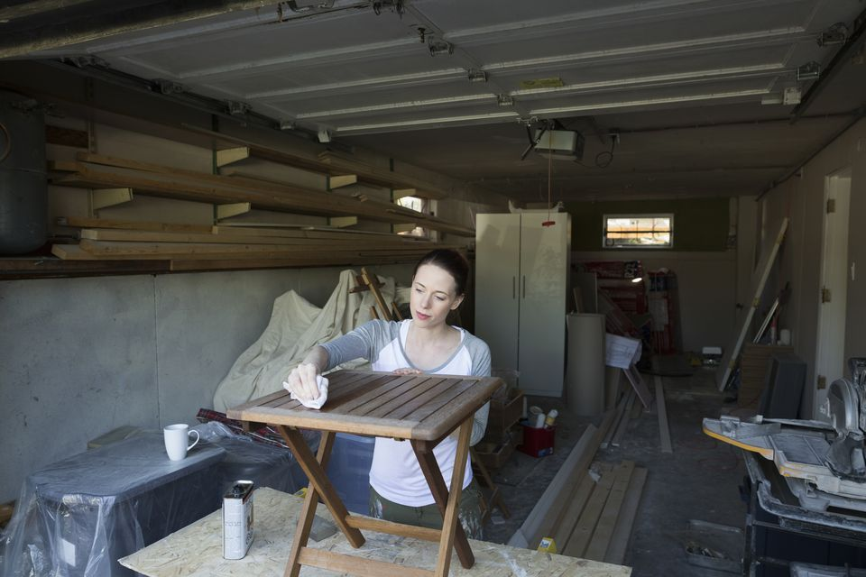 Woman staining wood furniture home improvement project in garage