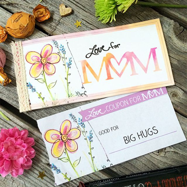 A coupon book for Mother's Day on a table with flowers and chocolate