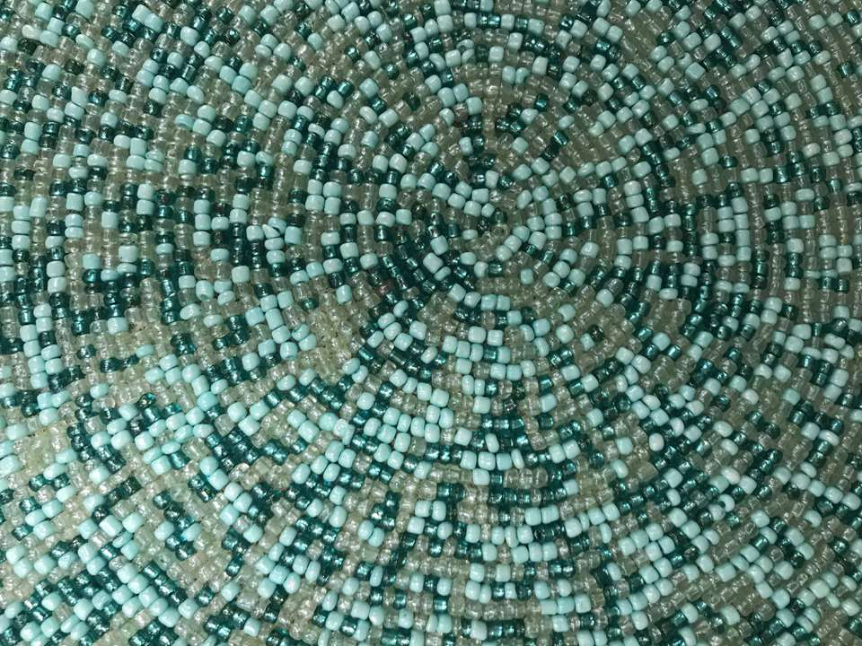 Part of a circular placemat made of plastic beads