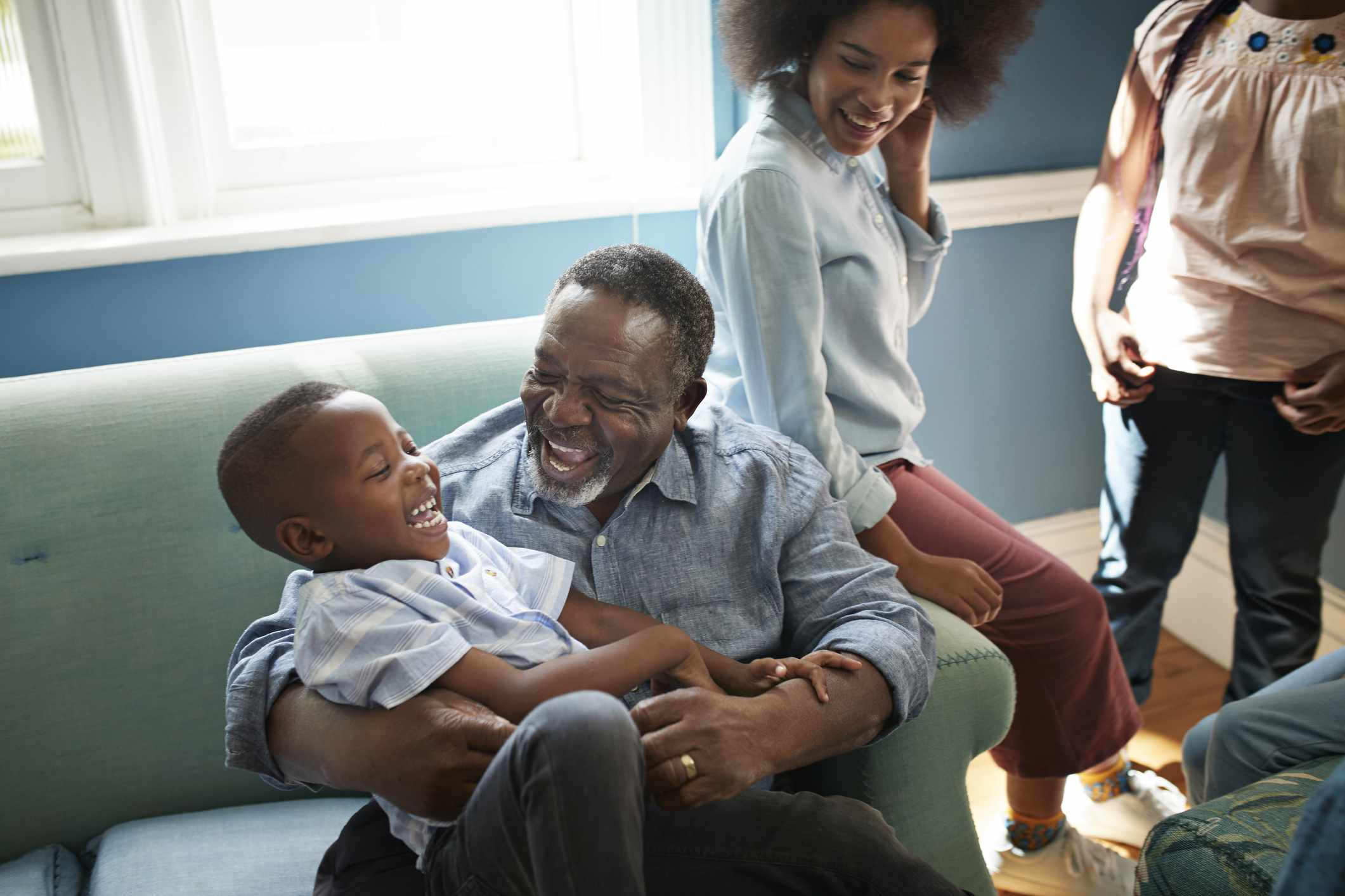 Happy man playing with boy on sofa at home
