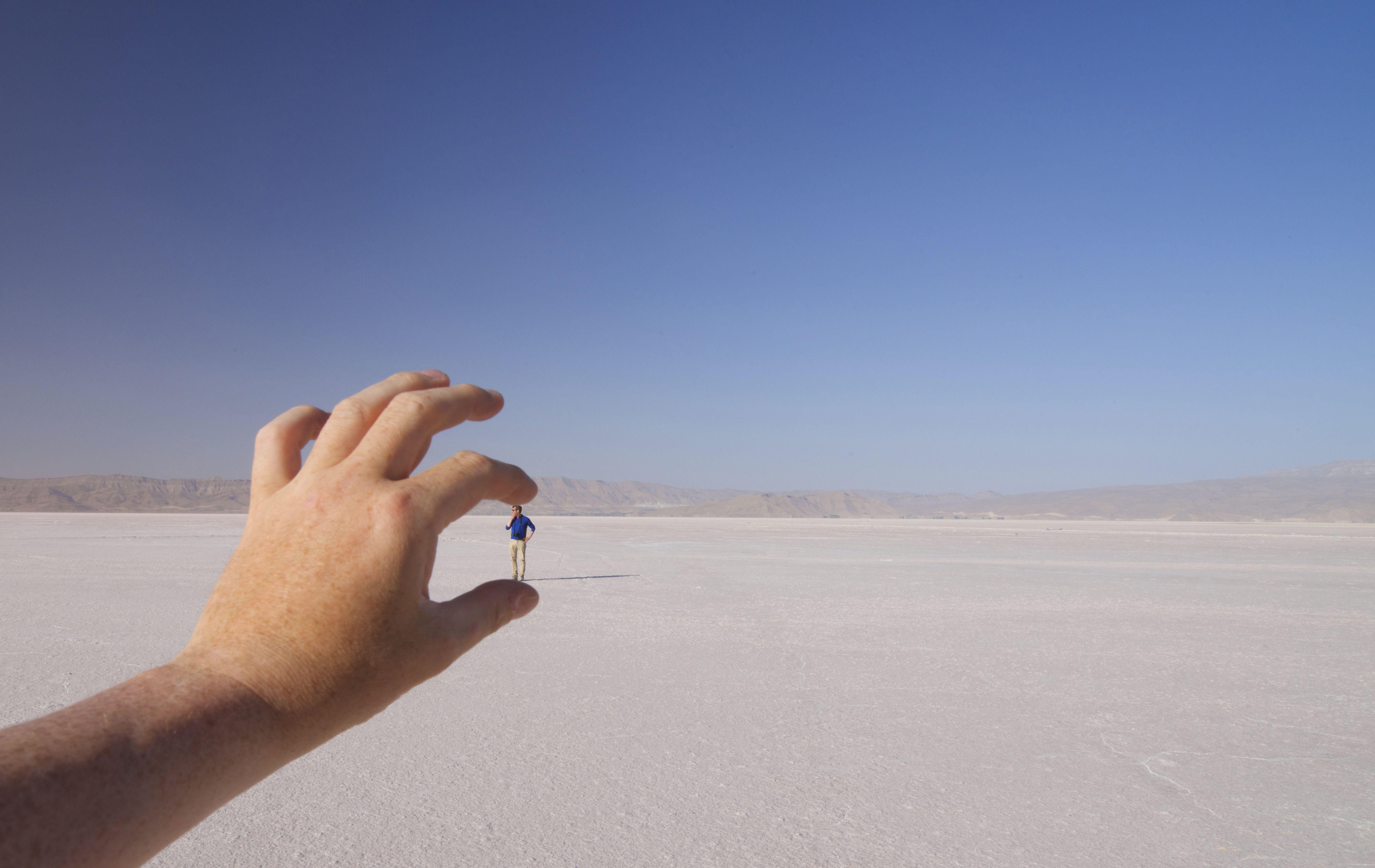 'Tiny tourist!' White salt desert backdrop. Maharlu Lake is a seasonal salt lake, Sarvestan County, near Shiraz, Iran