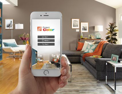 Hands holding a white smartphone in living room with the Home Depot app pulled up.