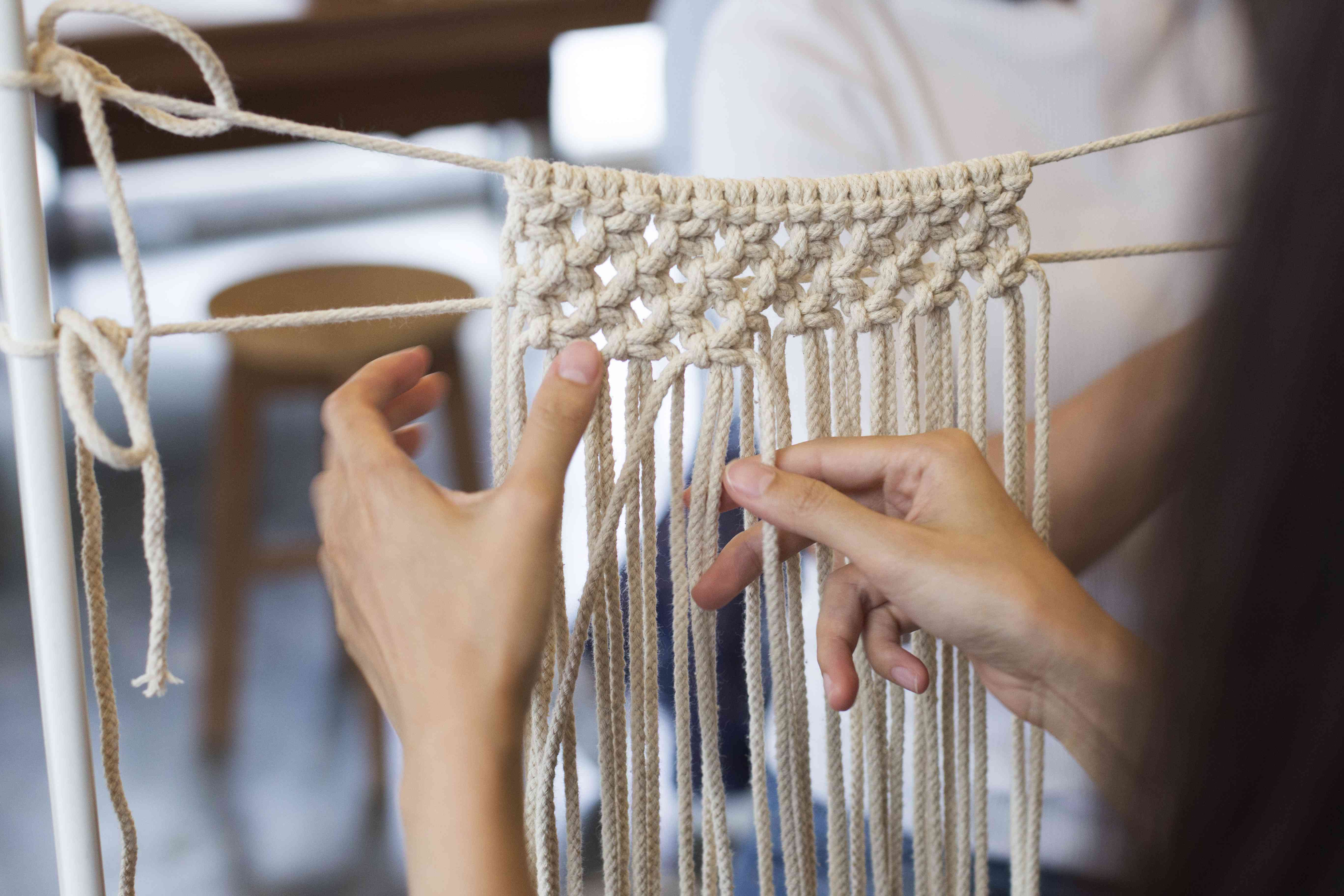 two hands doing macrame