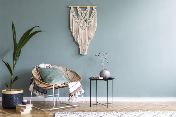 Stylish minimalistic interior of living room with design rattan armchair, black coffee table, tropical platn in basket, beige macrame on the wall and elegant accessories. Eucalyptus color of wall.