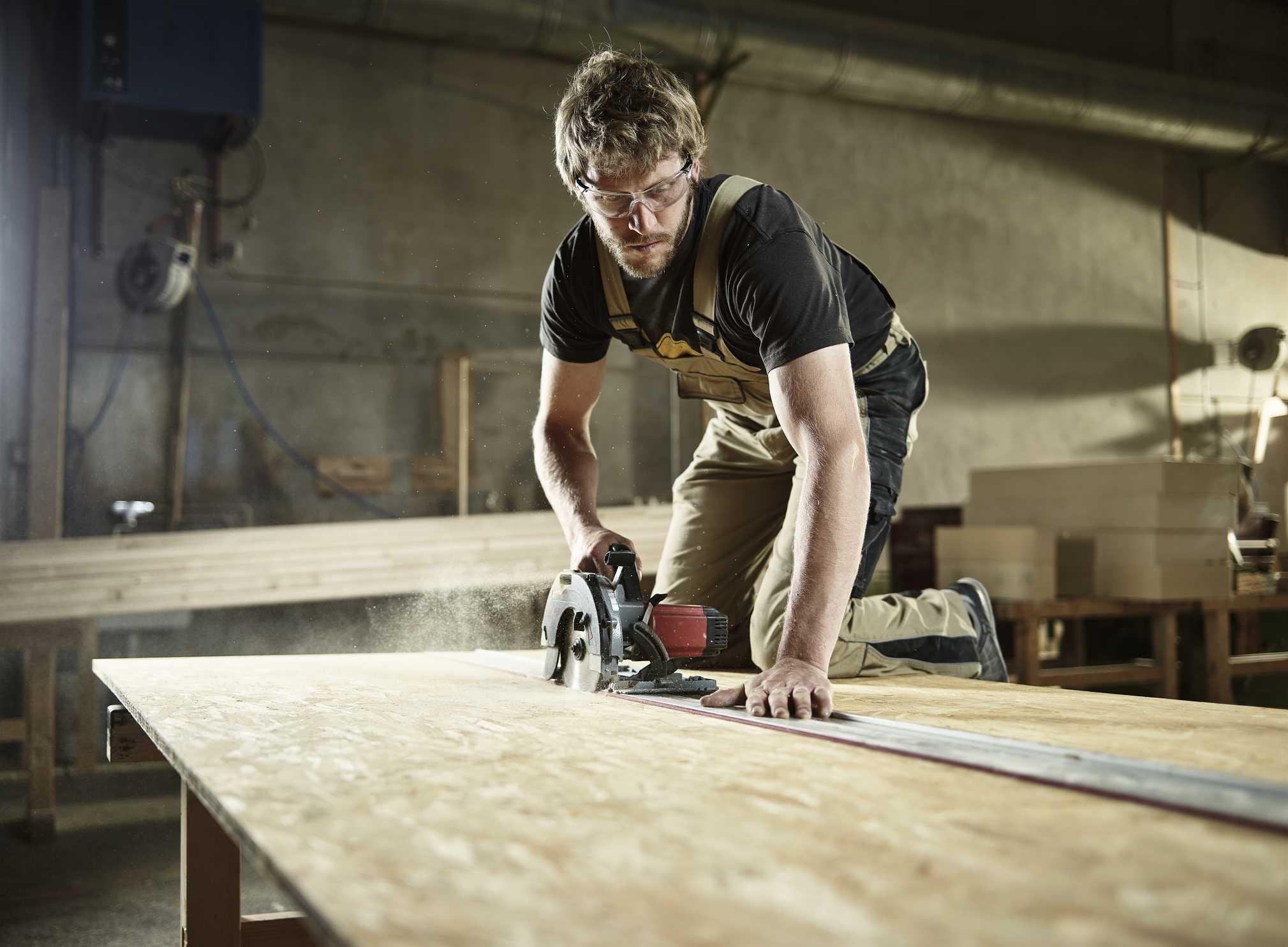 Man cutting a big plank of wood