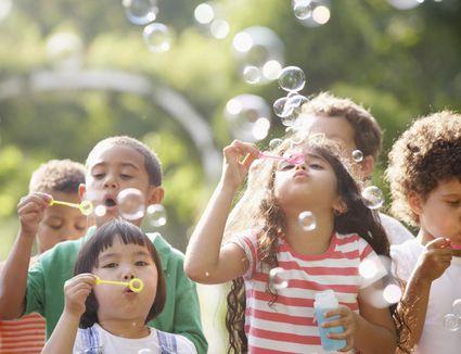 Children outdoors blowing bubbles.