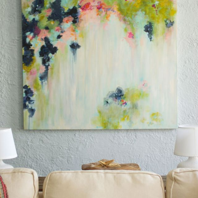 abstract painting hanging up behind a couch