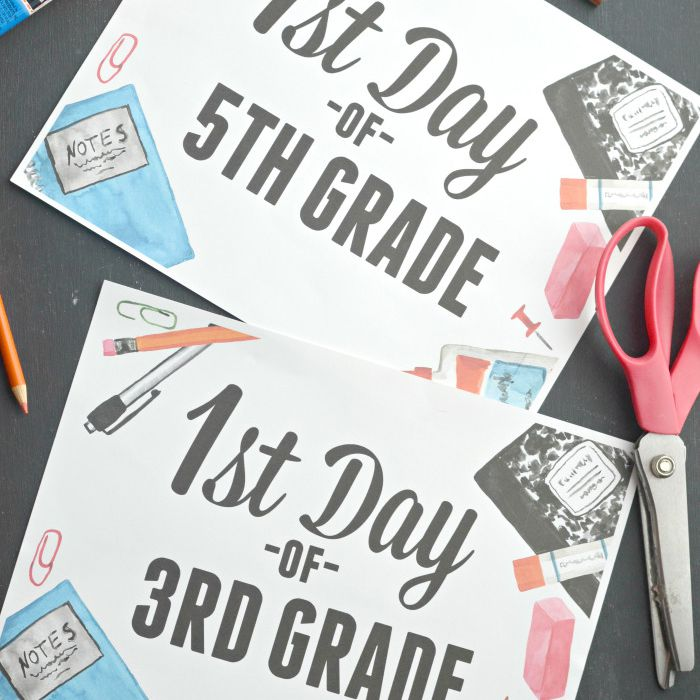 First day of school signs laying on a table with school supplies