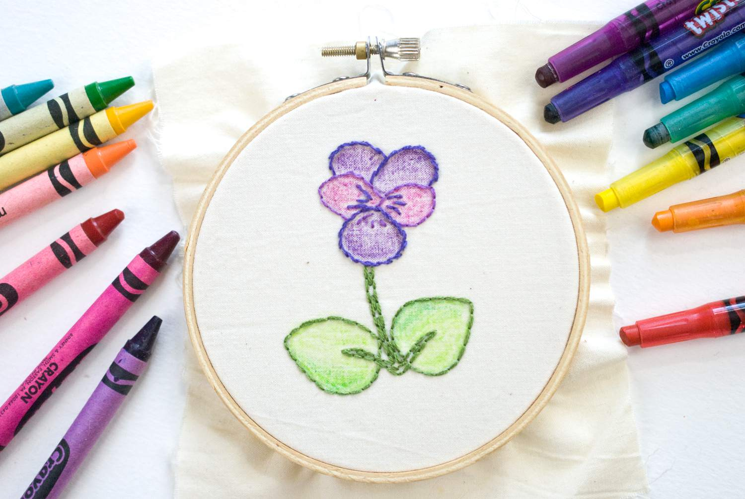 Embroidery in hoop with crayons surrounding the stitching.