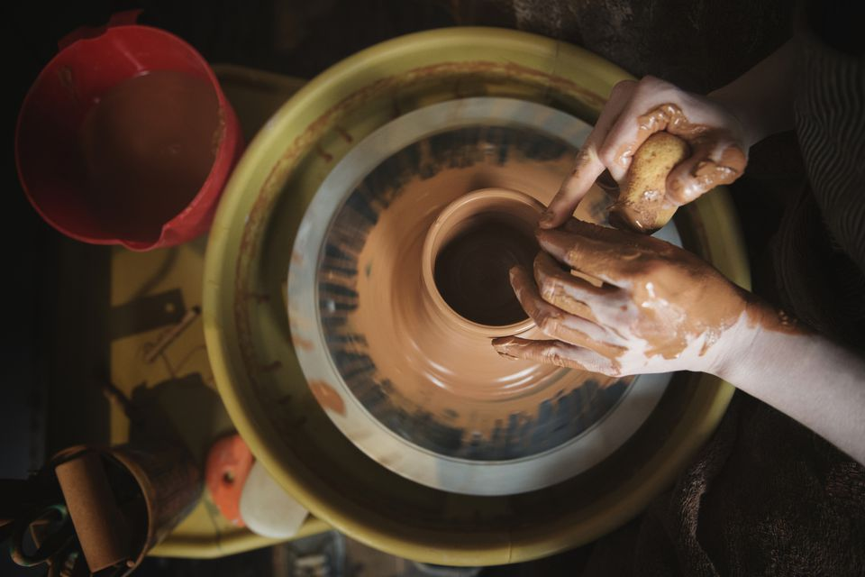 Hands of Caucasian woman shaping pottery clay on wheel