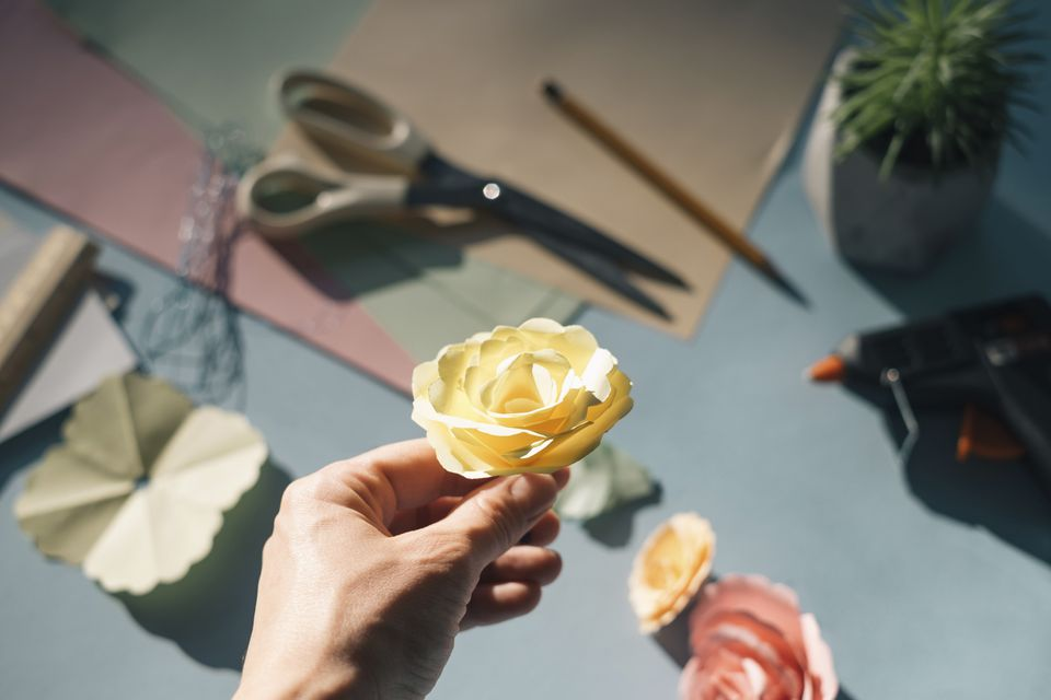 Female hand holding a paper rose