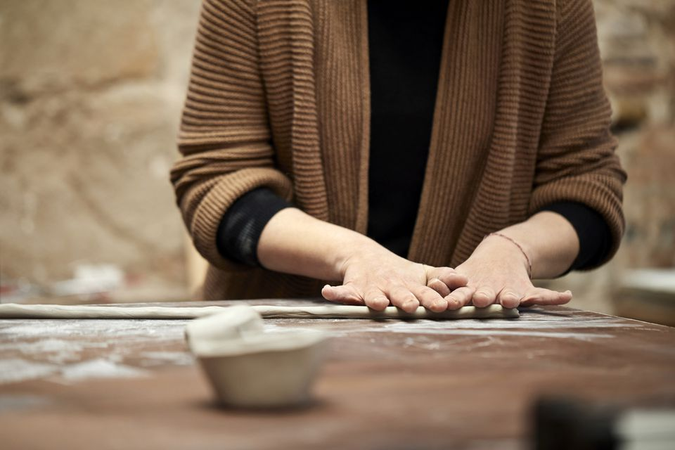 Female potter making clay coil at table