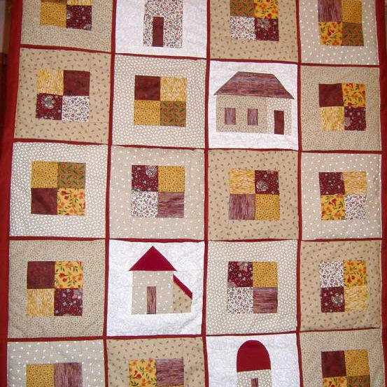 Person holding red quilt with houses and blocks of squares.