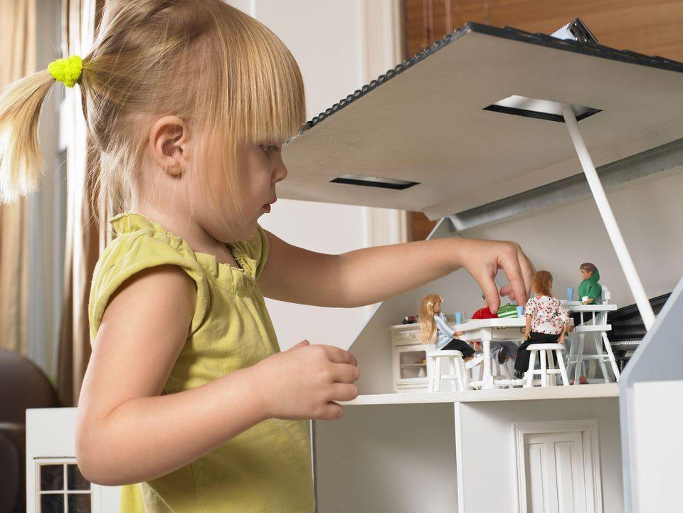 Girl setting dinner table in dollhouse