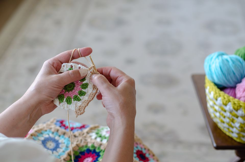 The woman is crocheting with colorful yarns.