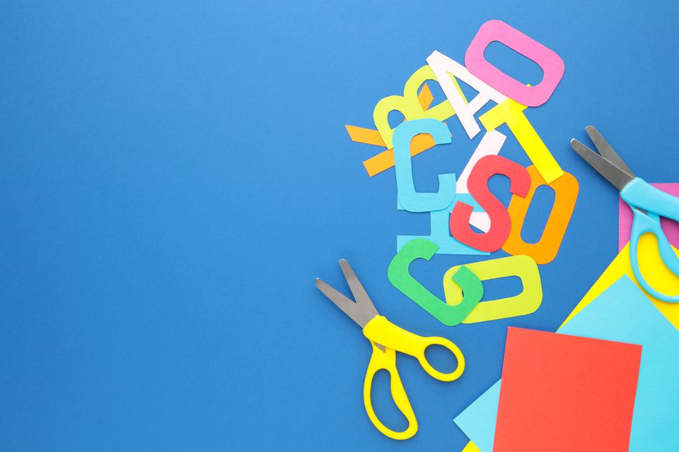 Scissors and colored paper for children's art on blue background