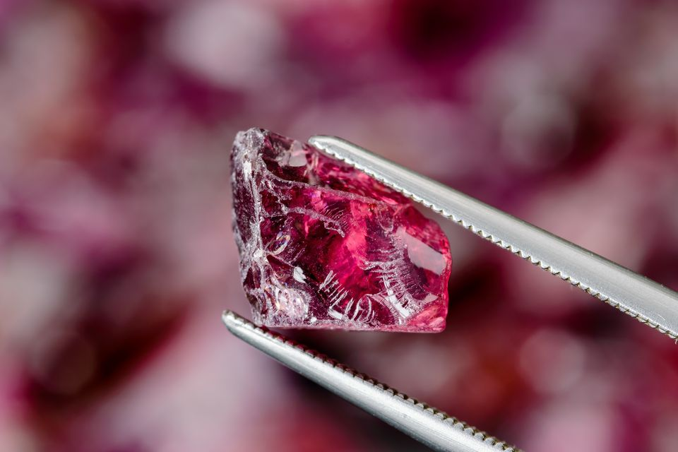 Rhodolite garnet between silver tweezers